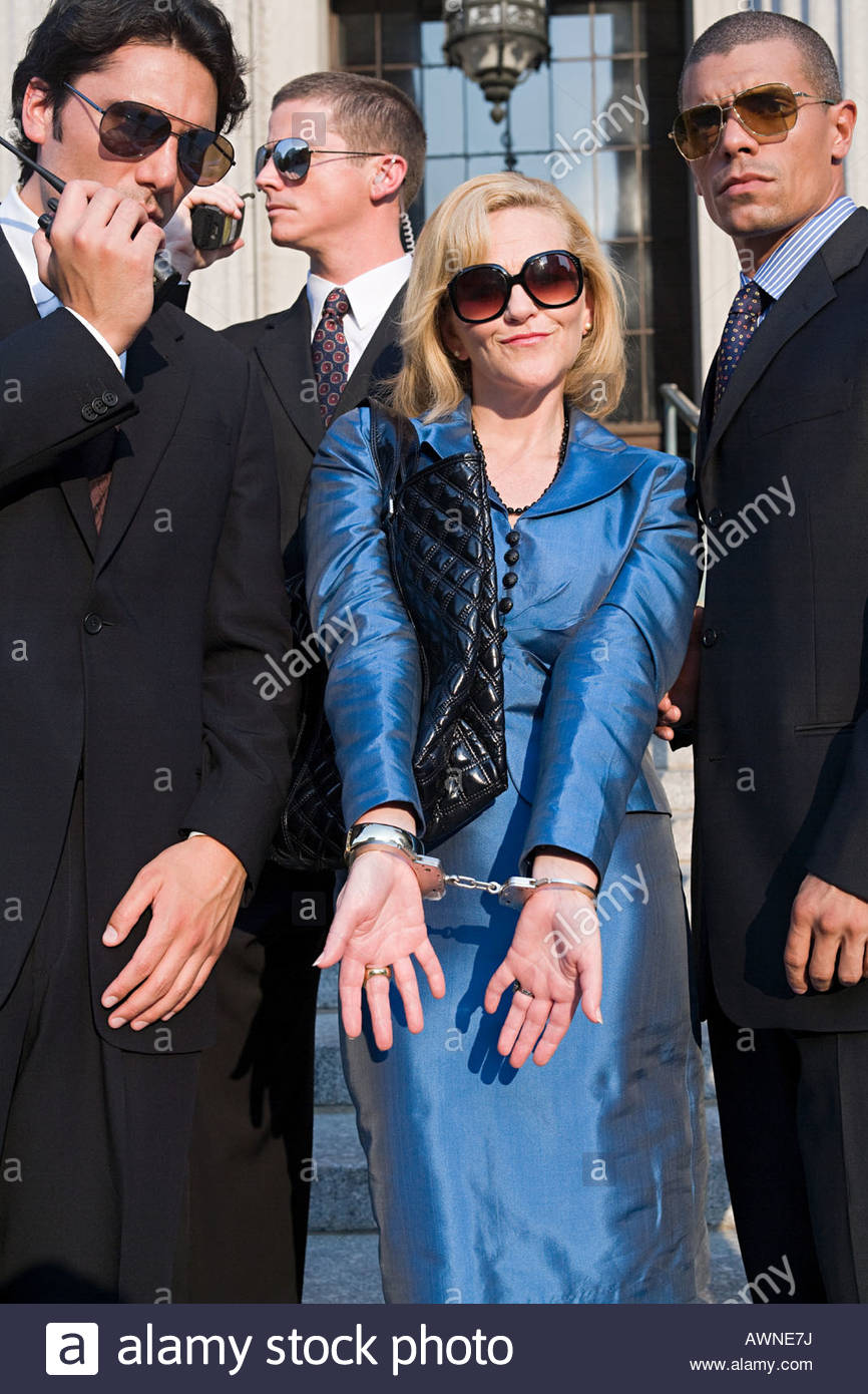 A woman in handcuffs with special agents - Stock Image
