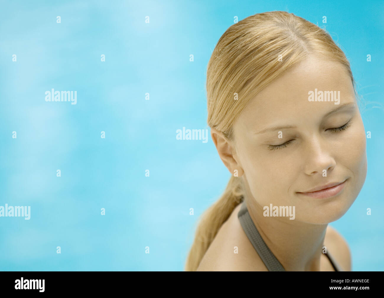 Woman smiling with eyes closed, water in background - Stock Image