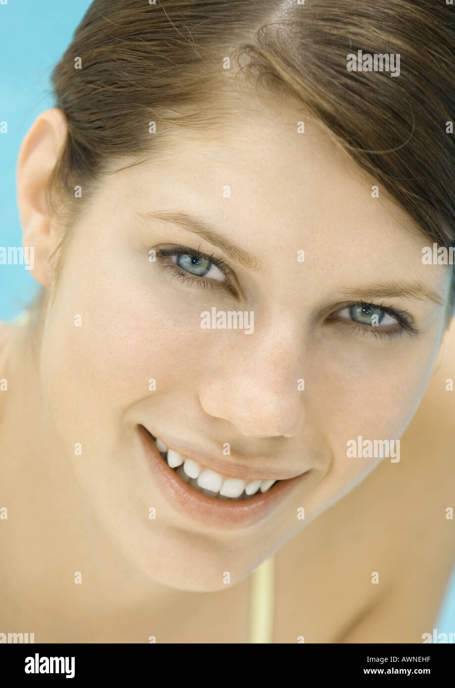 Young woman by pool, smiling, portrait - Stock Image