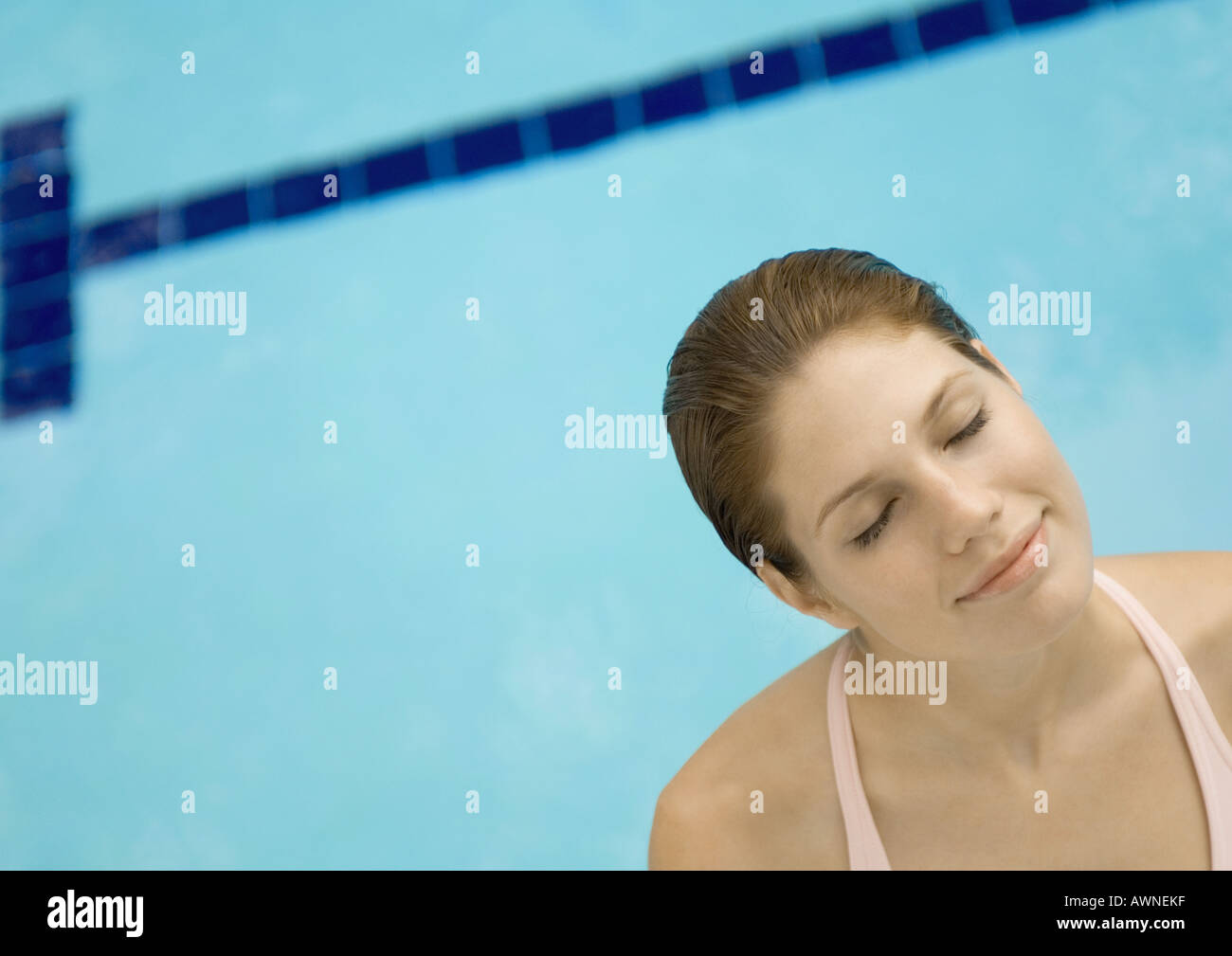 Woman standing by pool, eyes closed and head tilted - Stock Image