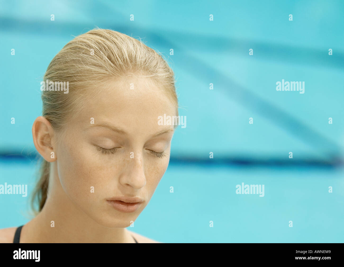 Woman, eyes closed, pool in background - Stock Image