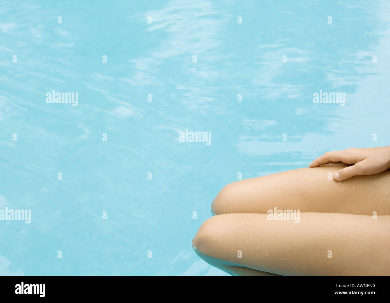 Woman sitting with legs in pool, cropped view of legs - Stock Image