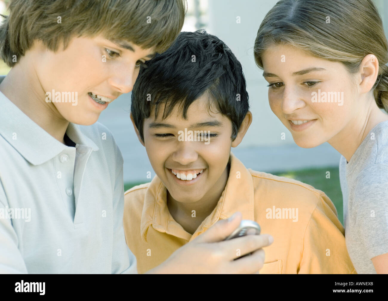 Preteen friends looking at cell phone - Stock Image