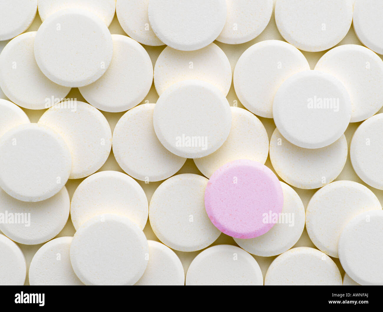 A pink tablet amongst white tablets - Stock Image