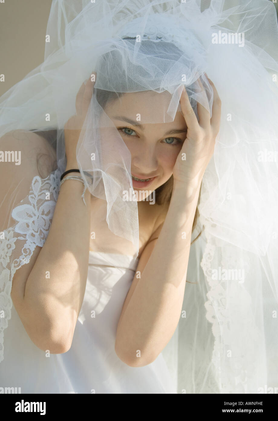 Preteen girl dressed up as bride - Stock Image