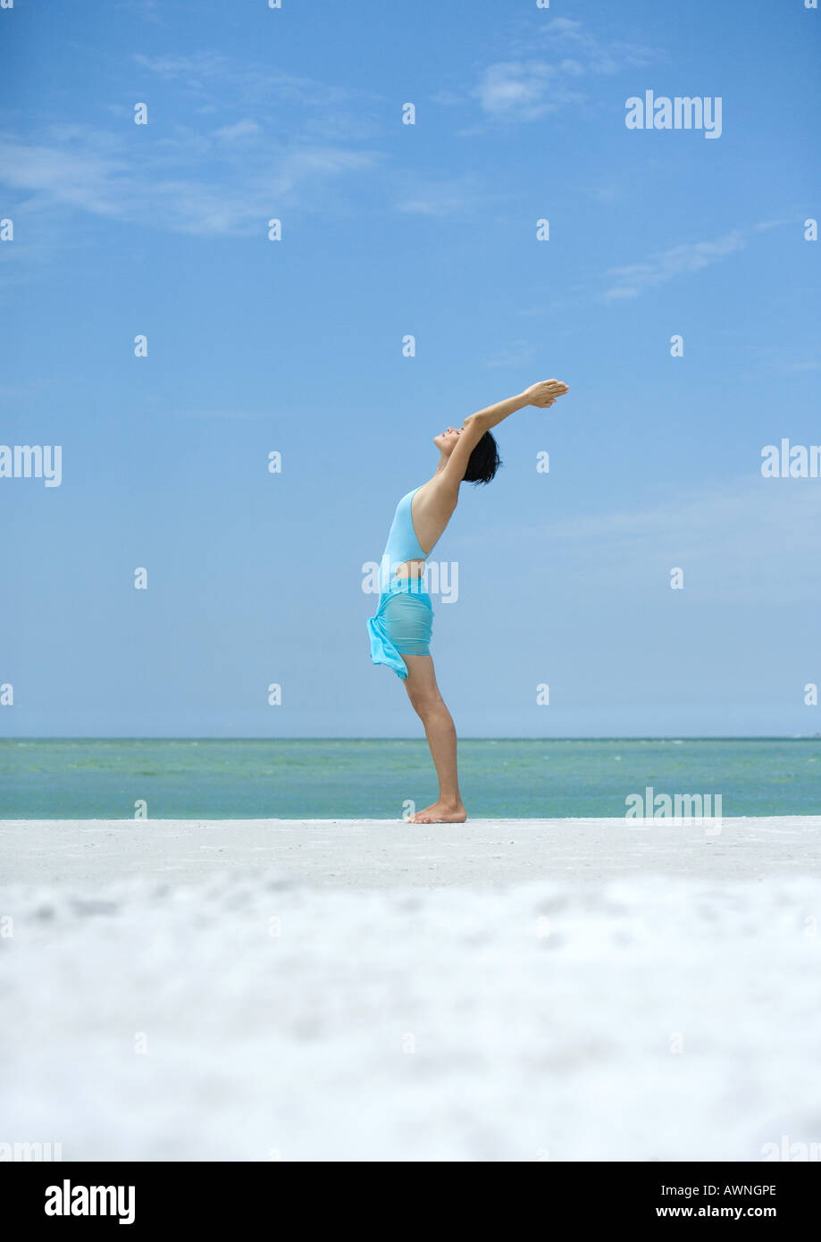 Woman performing sun salutation on beach - Stock Image