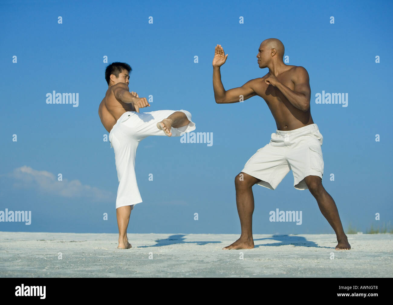 Two men practicing martial arts on beach - Stock Image