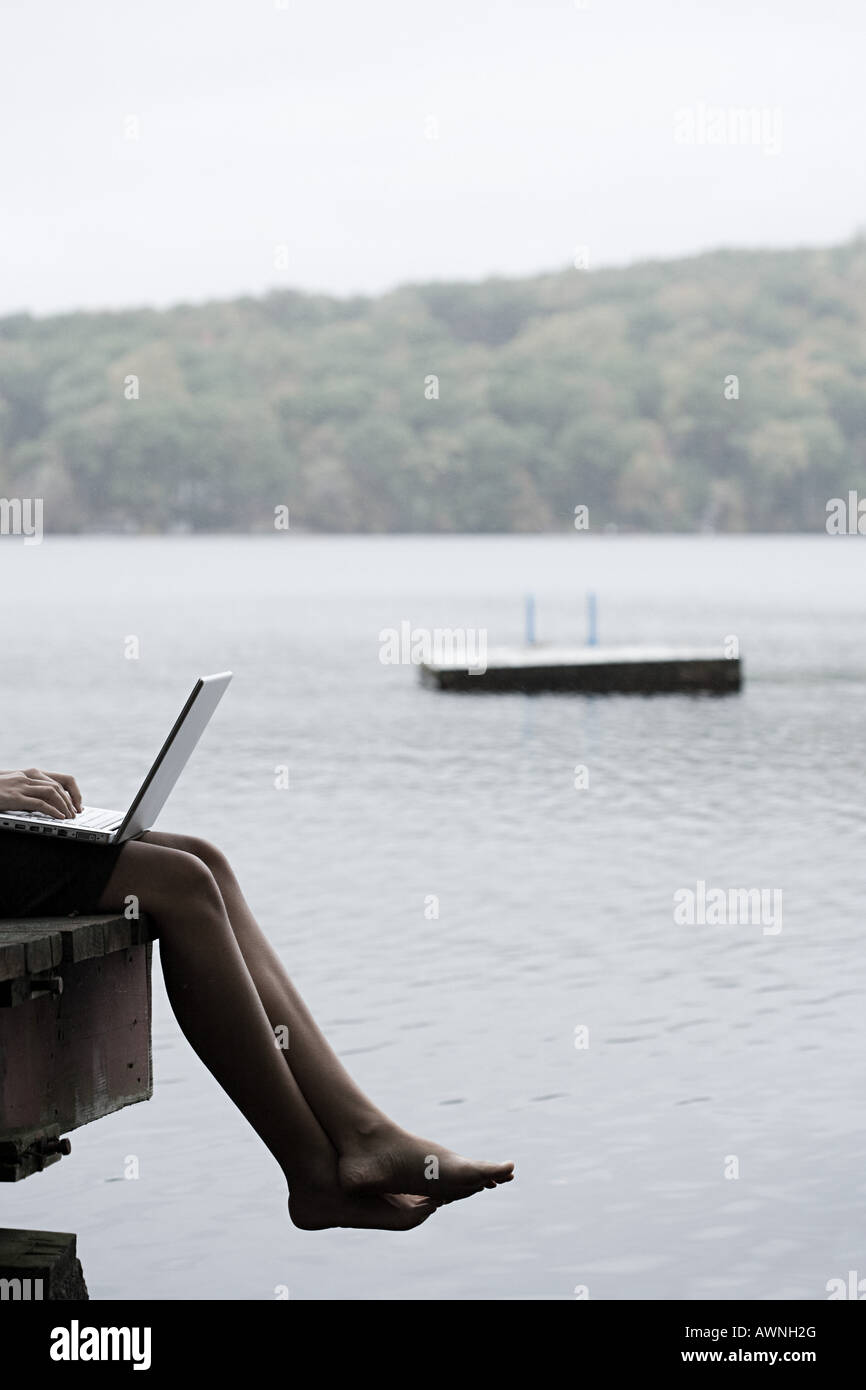 A woman with a laptop sat on a jetty - Stock Image