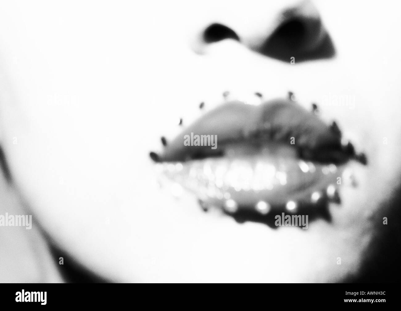 Woman's mouth with jewel adornments, close up of lower face, black and white, blurred. - Stock Image