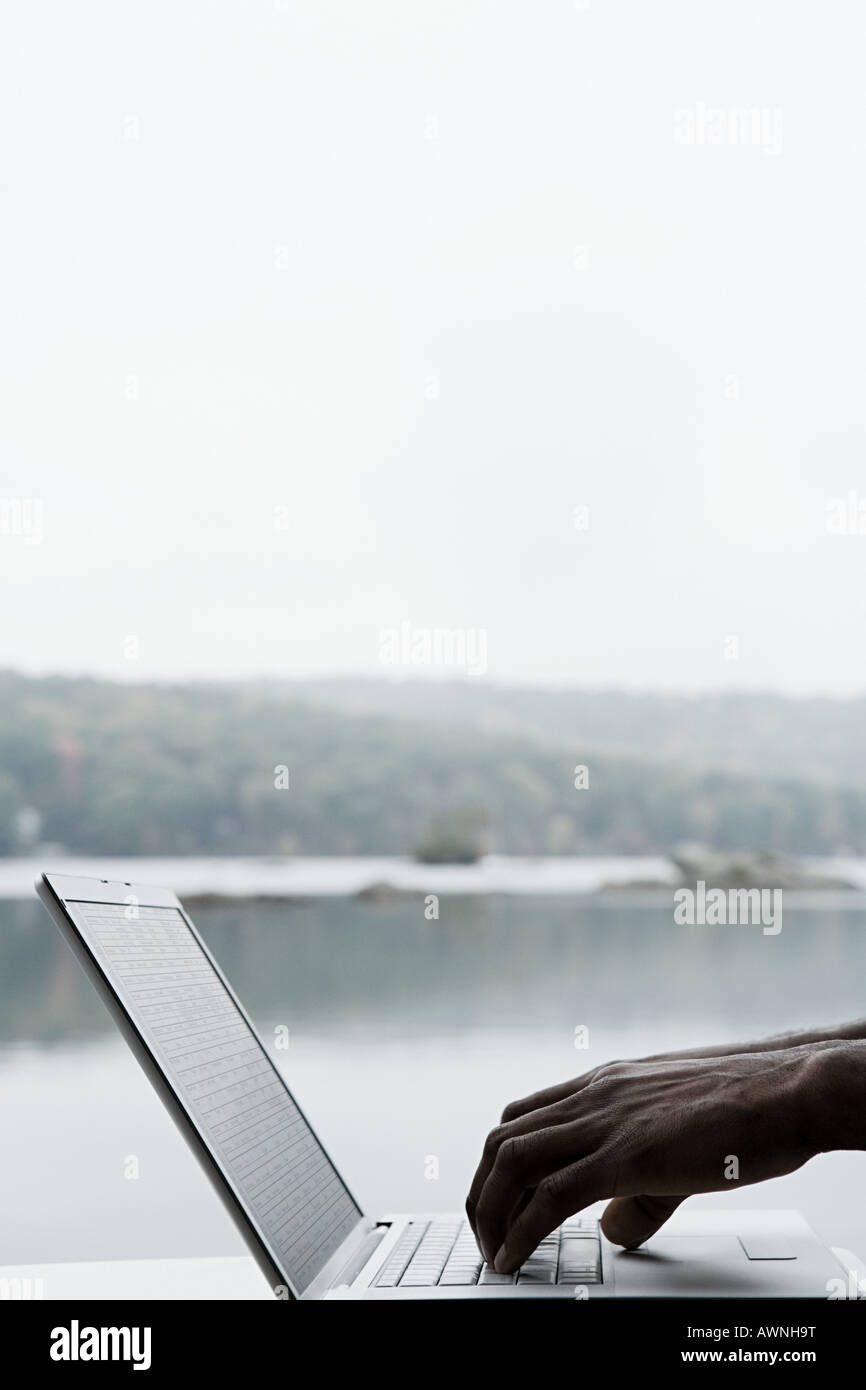 A persons hands typing on a laptop - Stock Image