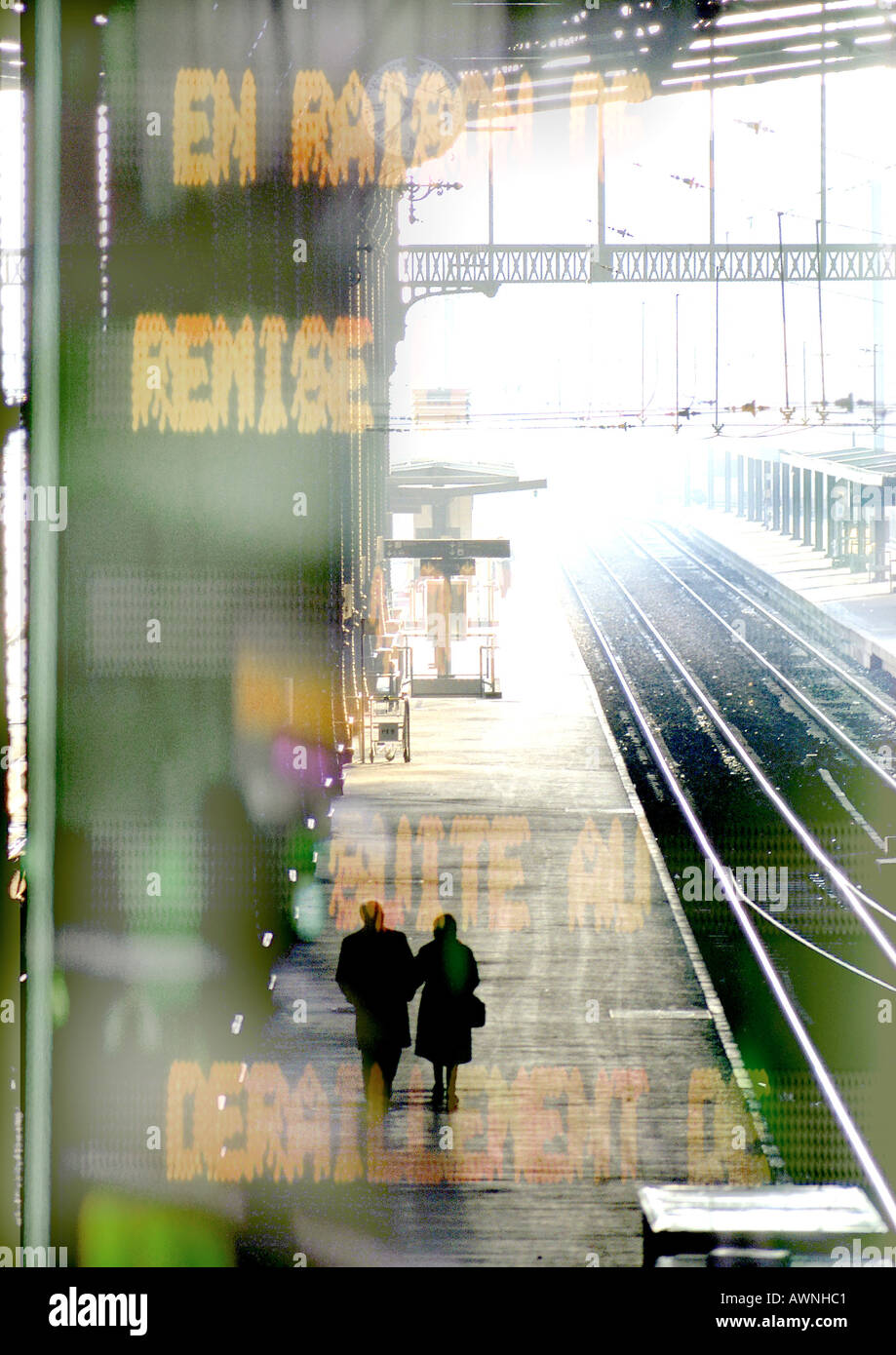 Couple walking on train platform, information sign superimposed - Stock Image