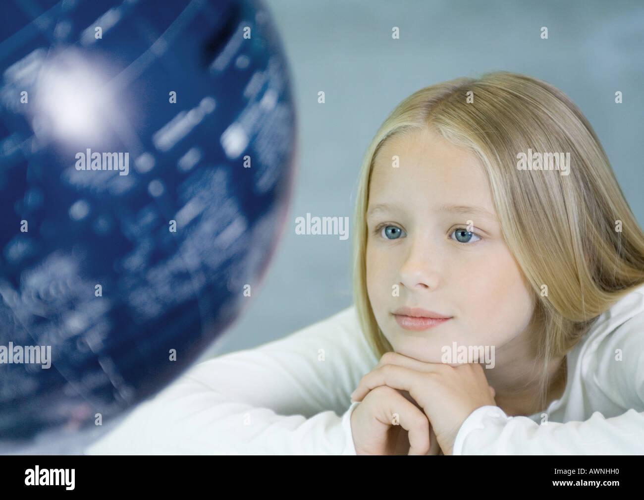 Girl looking at globe - Stock Image