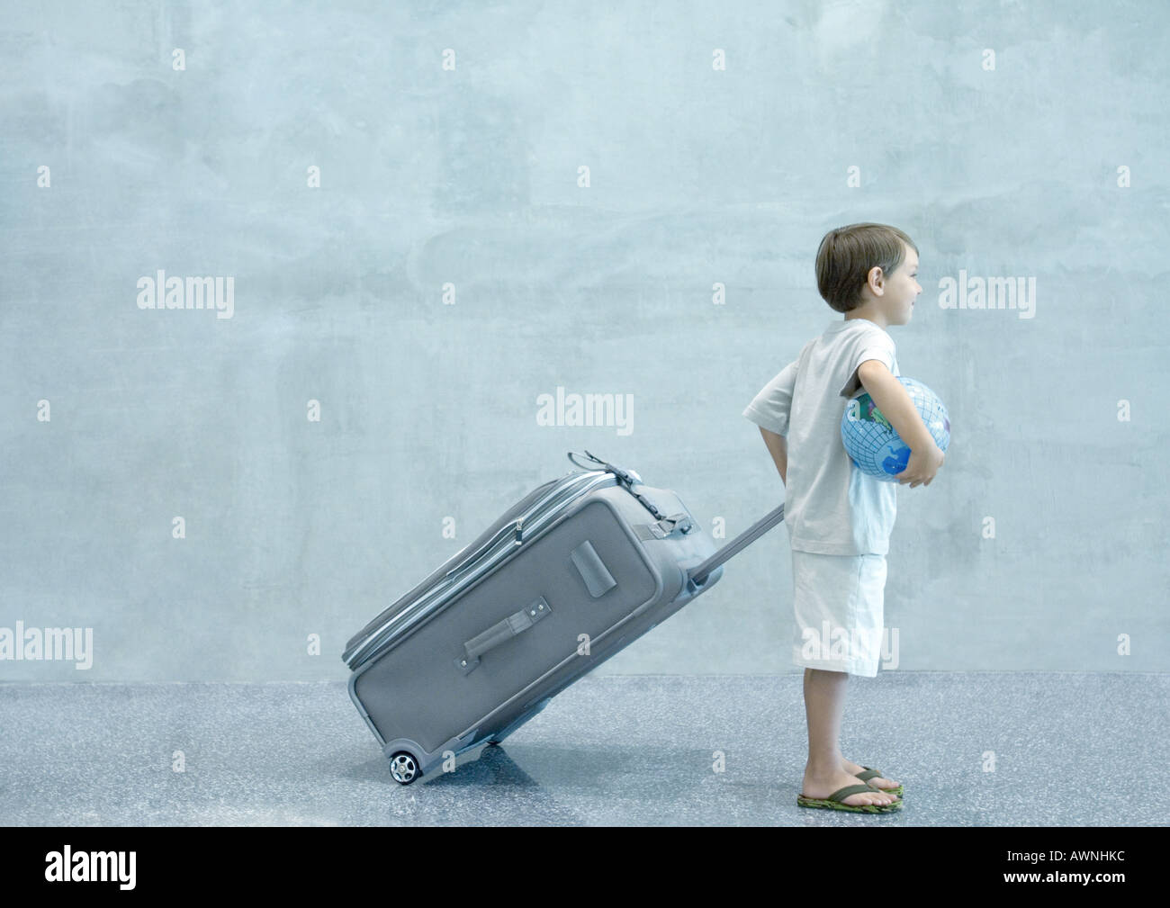 Boy with suitcase and globe - Stock Image