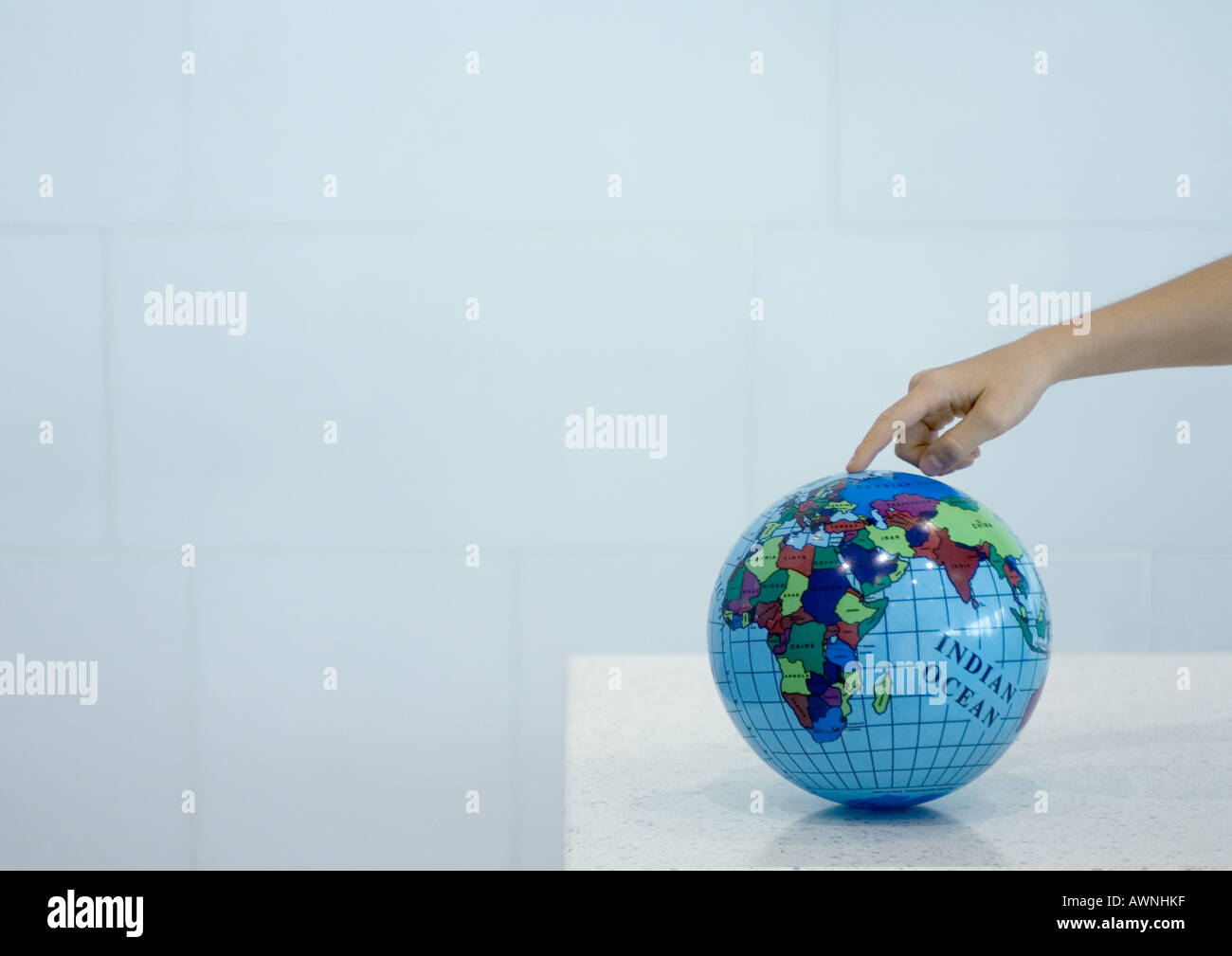 Child's hand pointing to spot on globe - Stock Image