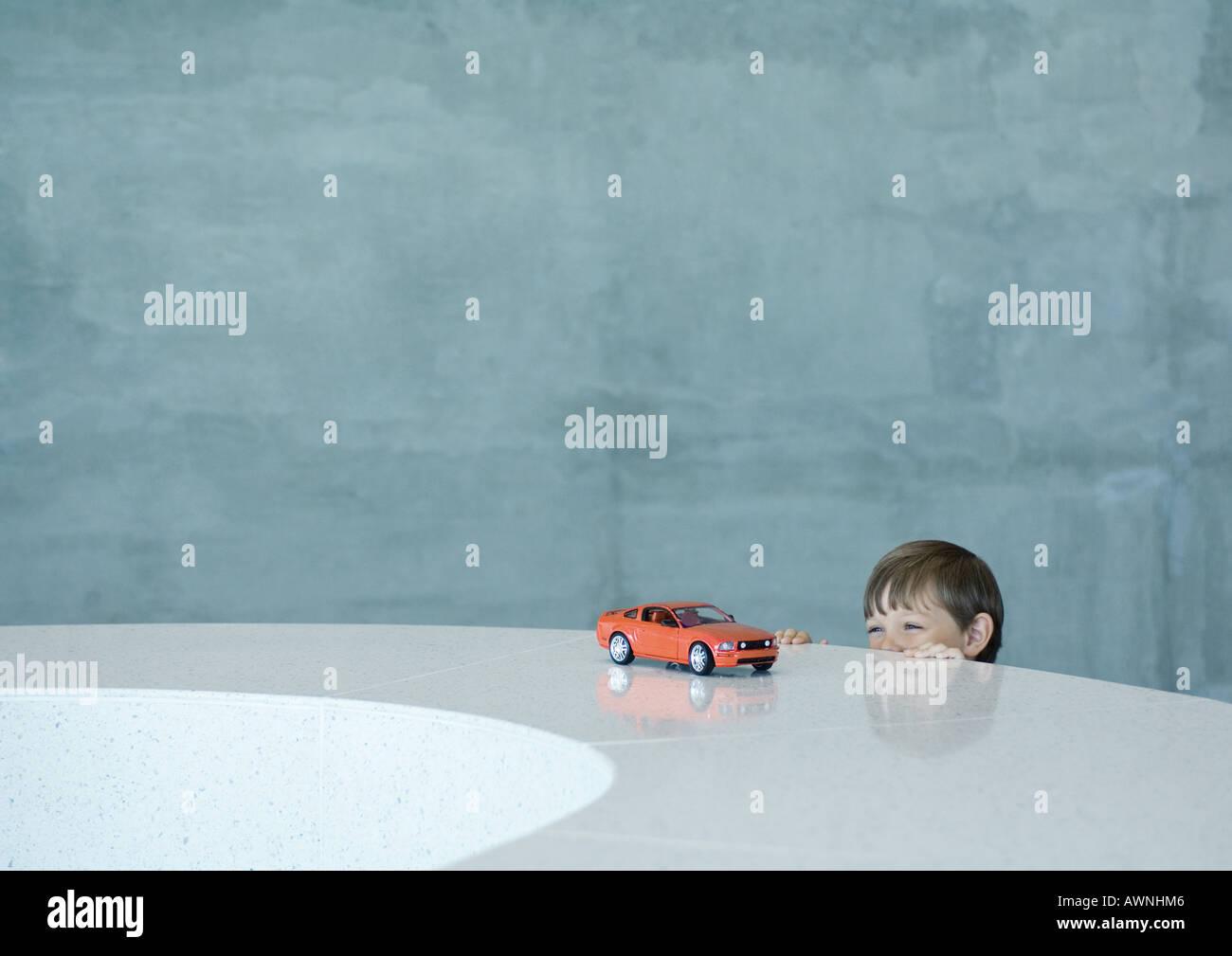 Boy peeking at toy sports car - Stock Image