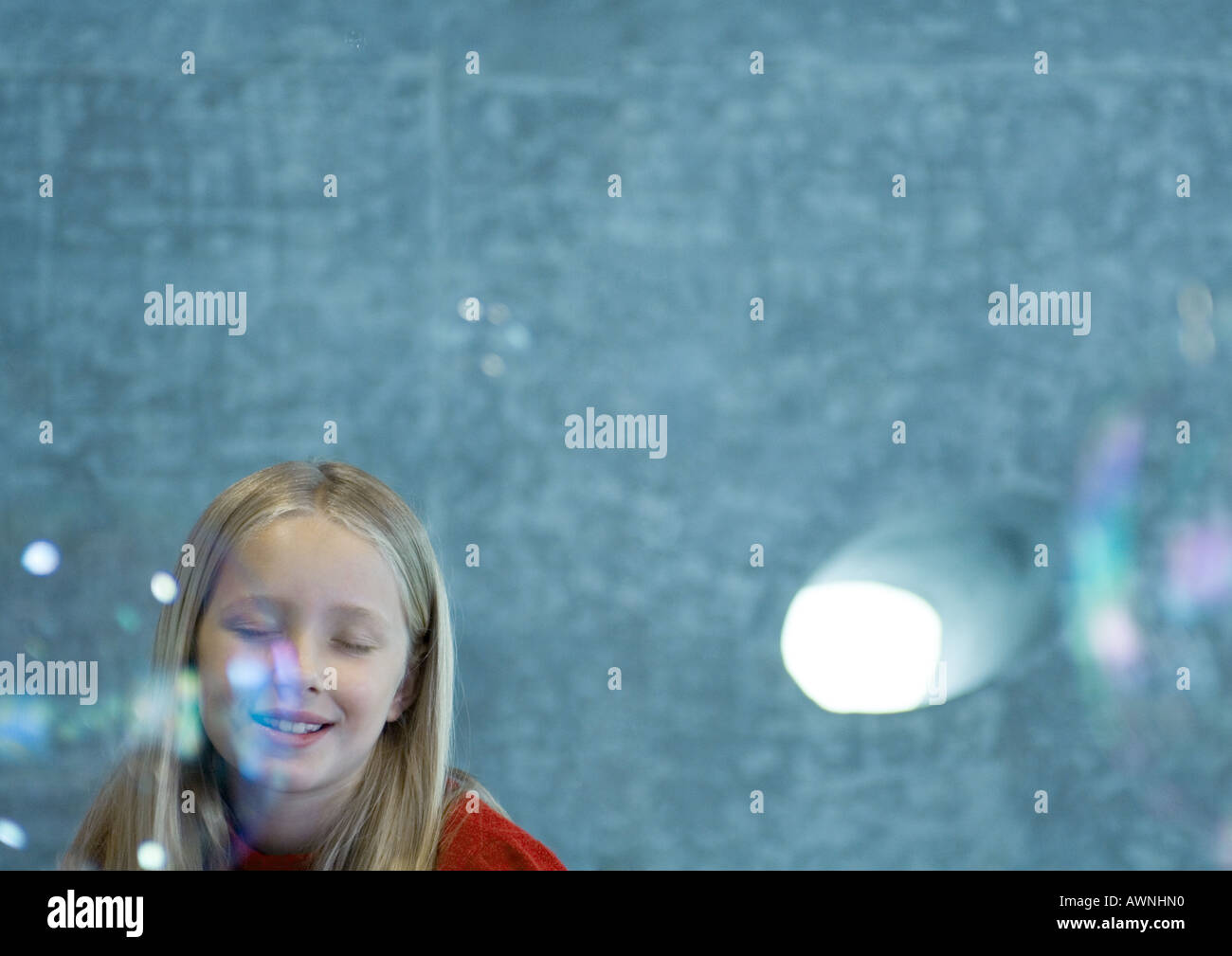 Girl closing eyes as bubbles float in the air - Stock Image