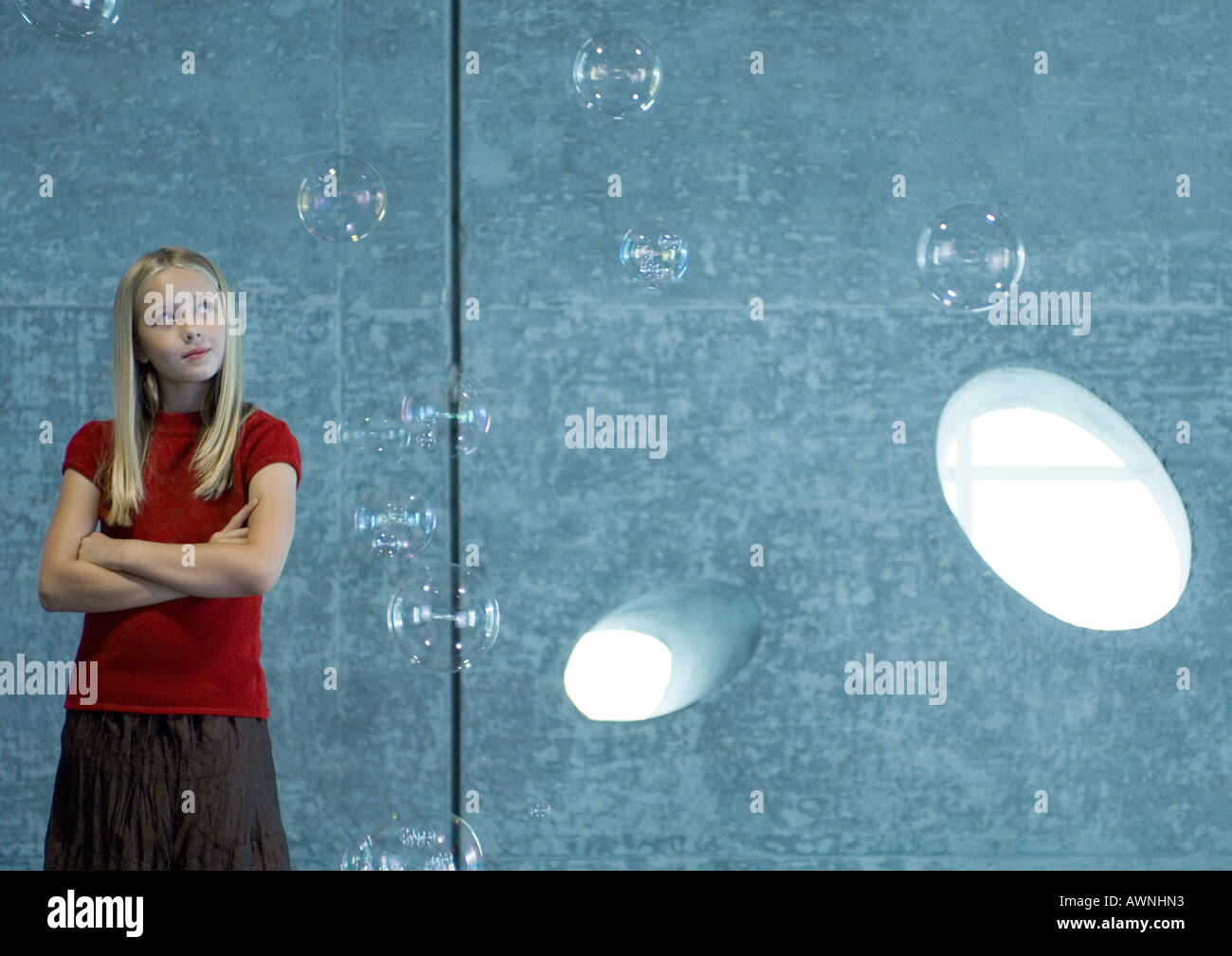 Girl watching bubbles float in the air - Stock Image