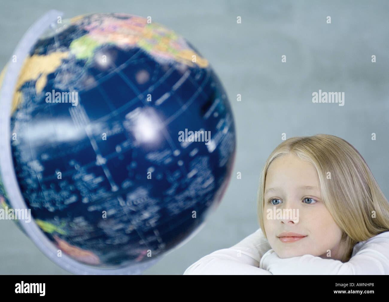 Girl looking at globe - Stock Image
