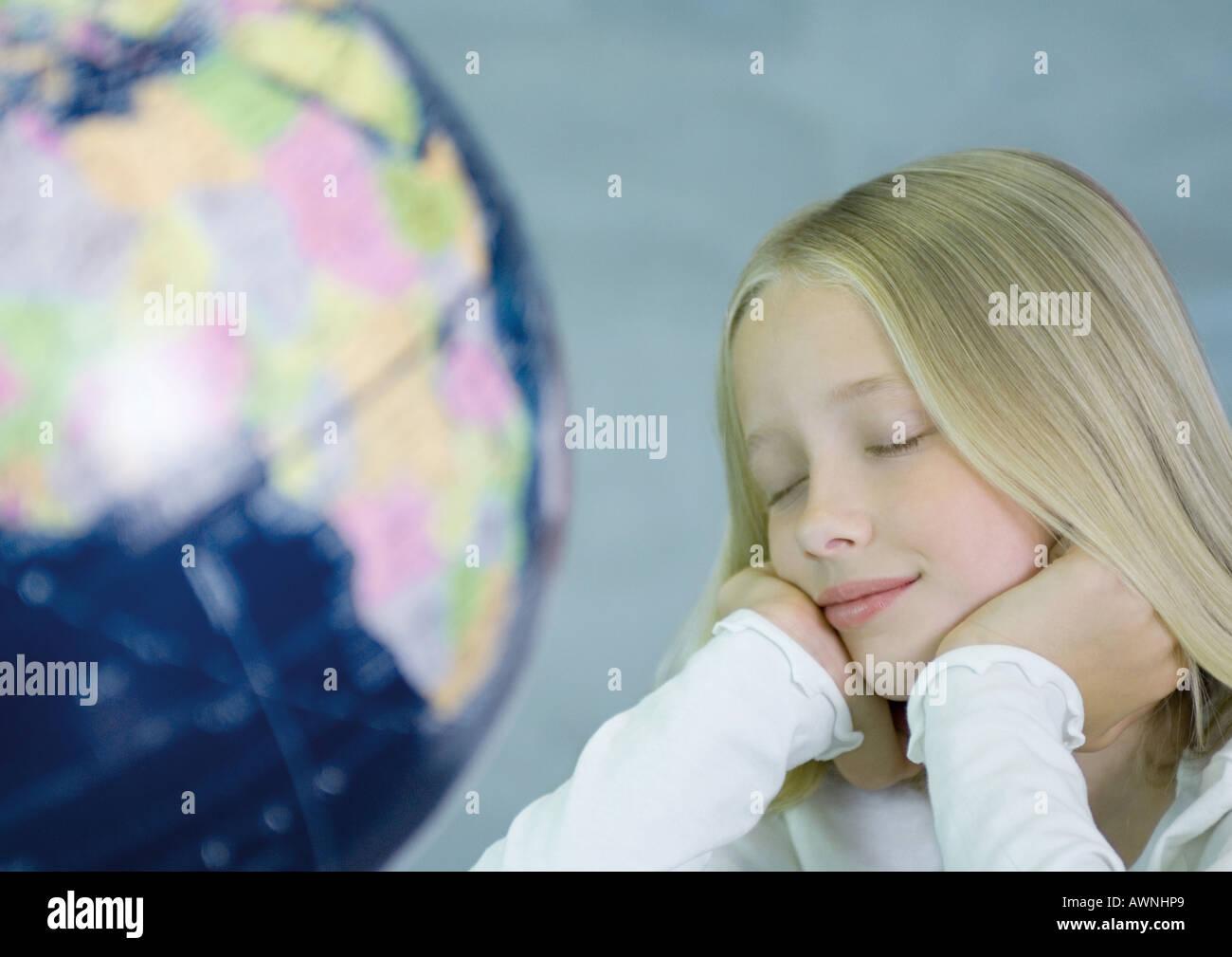 Girl next to globe, eyes closed - Stock Image