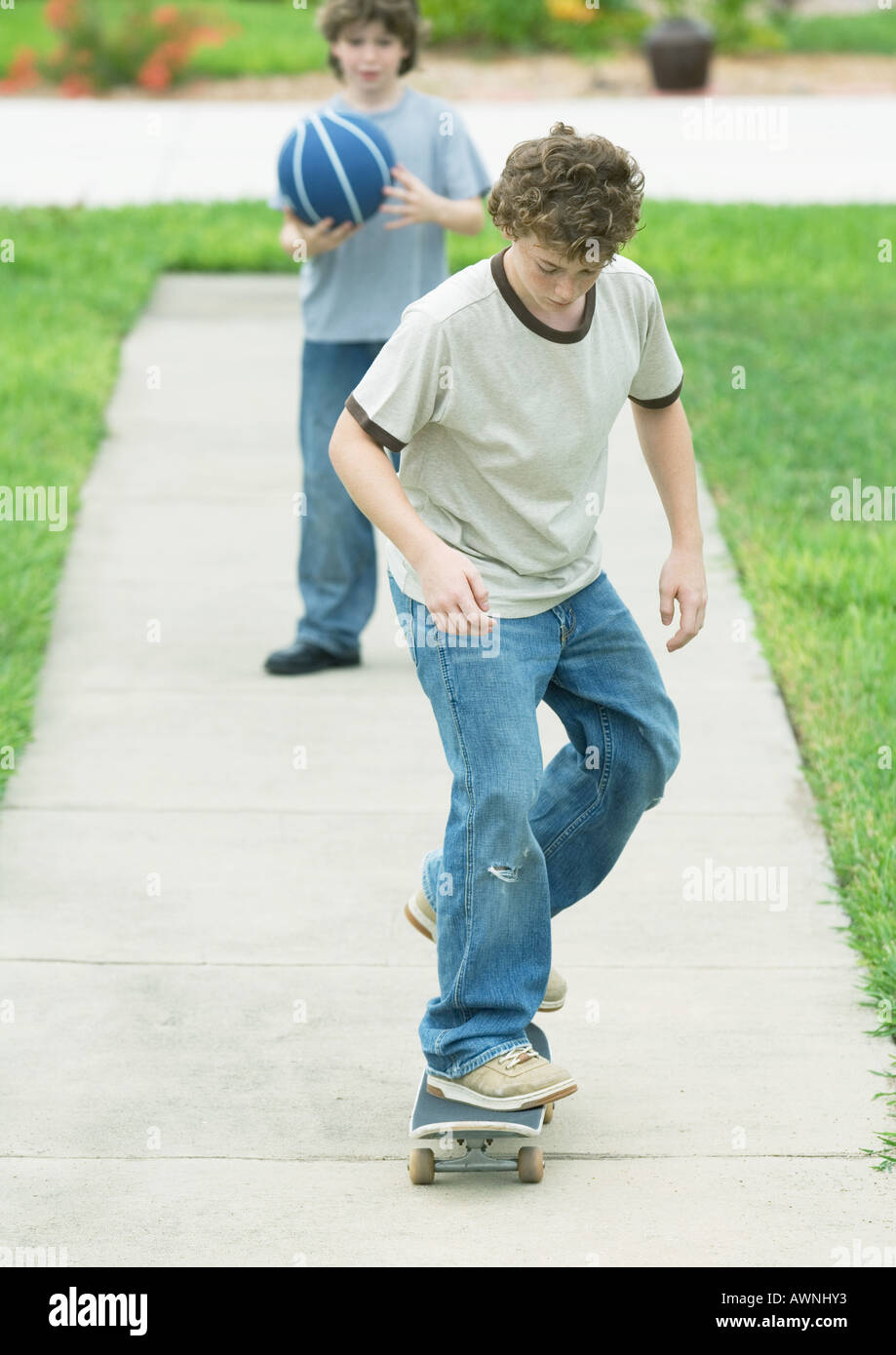 Boy skating on suburban sidewalk - Stock Image