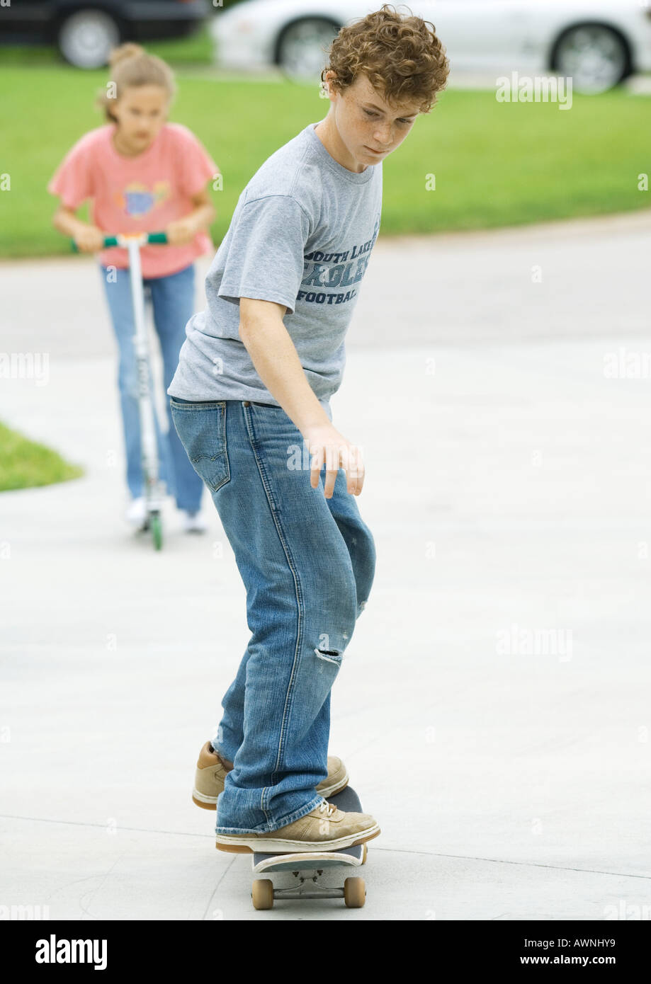 Suburban children playing in driveway - Stock Image