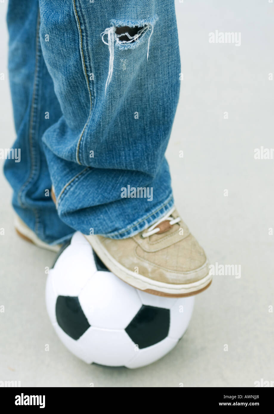 Boy resting foot on soccer ball, close-up - Stock Image