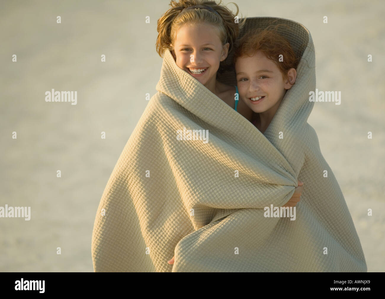 Two girls wrapped in blanket on beach - Stock Image
