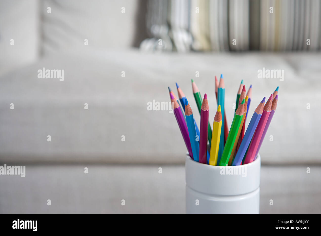 Coloured pencils in a desk tidy - Stock Image