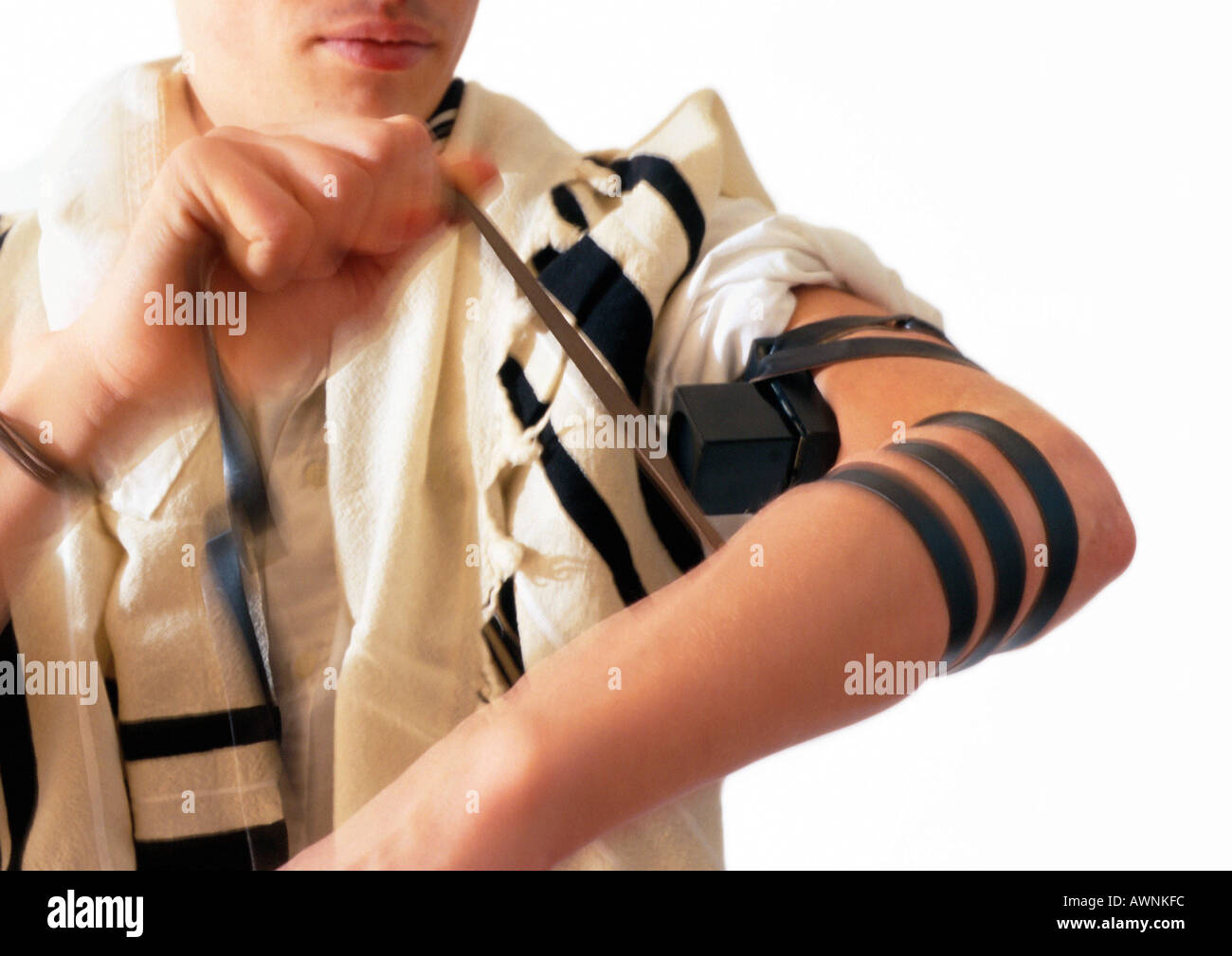 Jewish man wrapping arm with straps of Teffilin - Stock Image