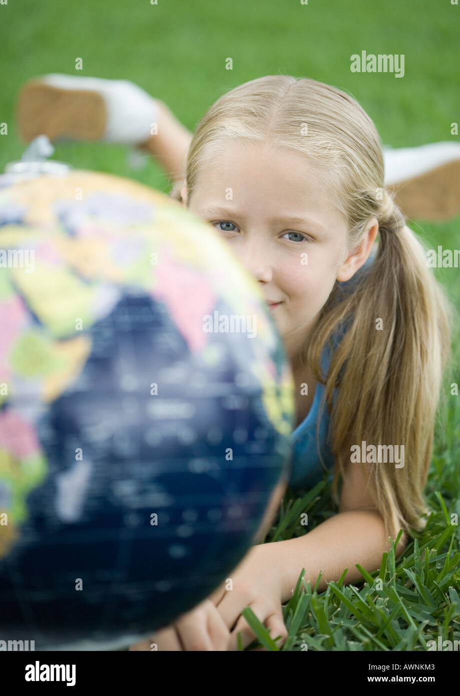 Girl lying on grass, globe in foreground - Stock Image