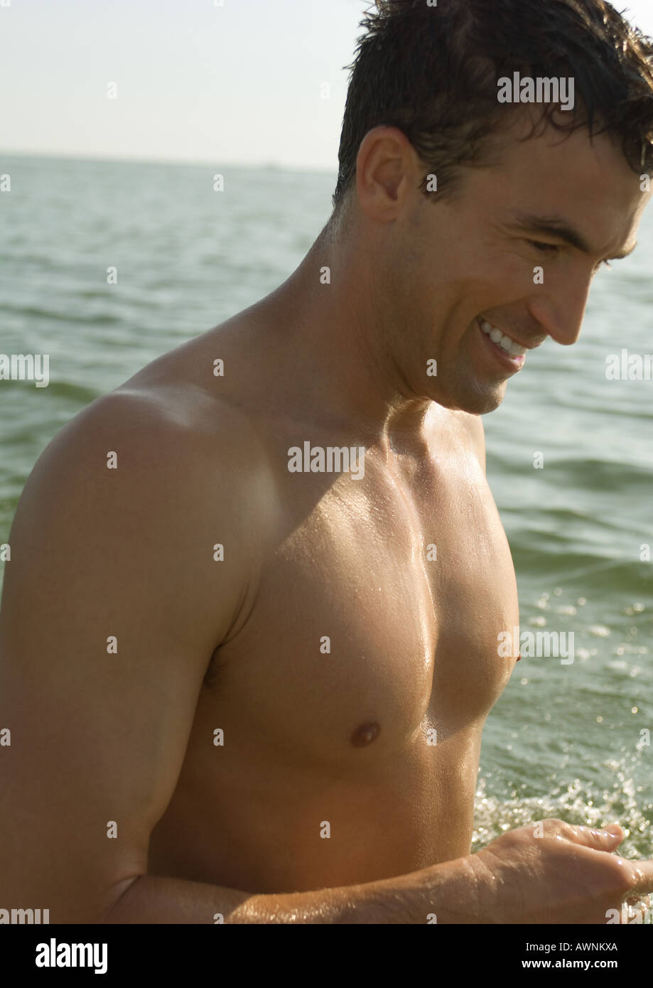 Barechested man, sea in background - Stock Image
