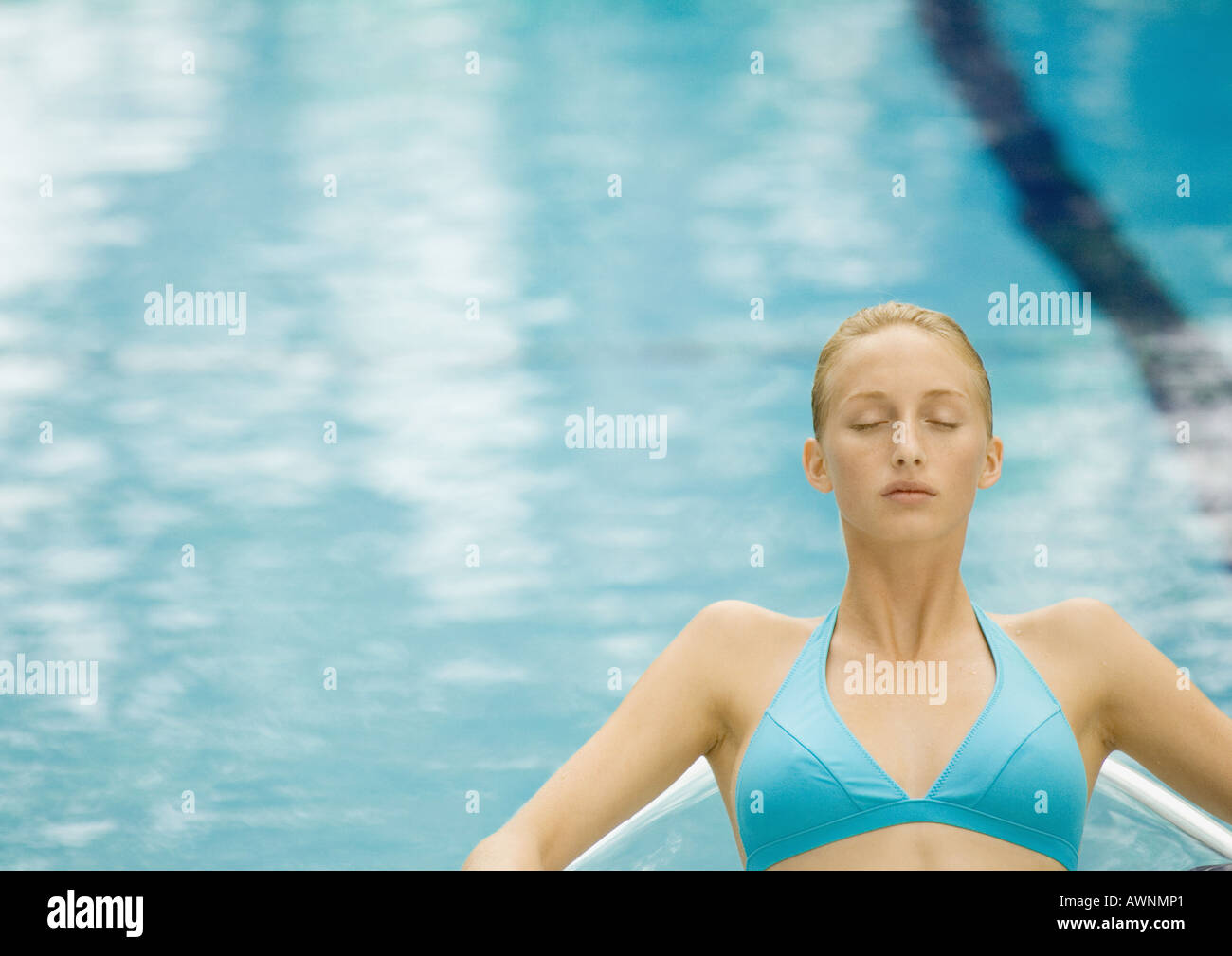 Woman relaxing near pool, eyes closed - Stock Image