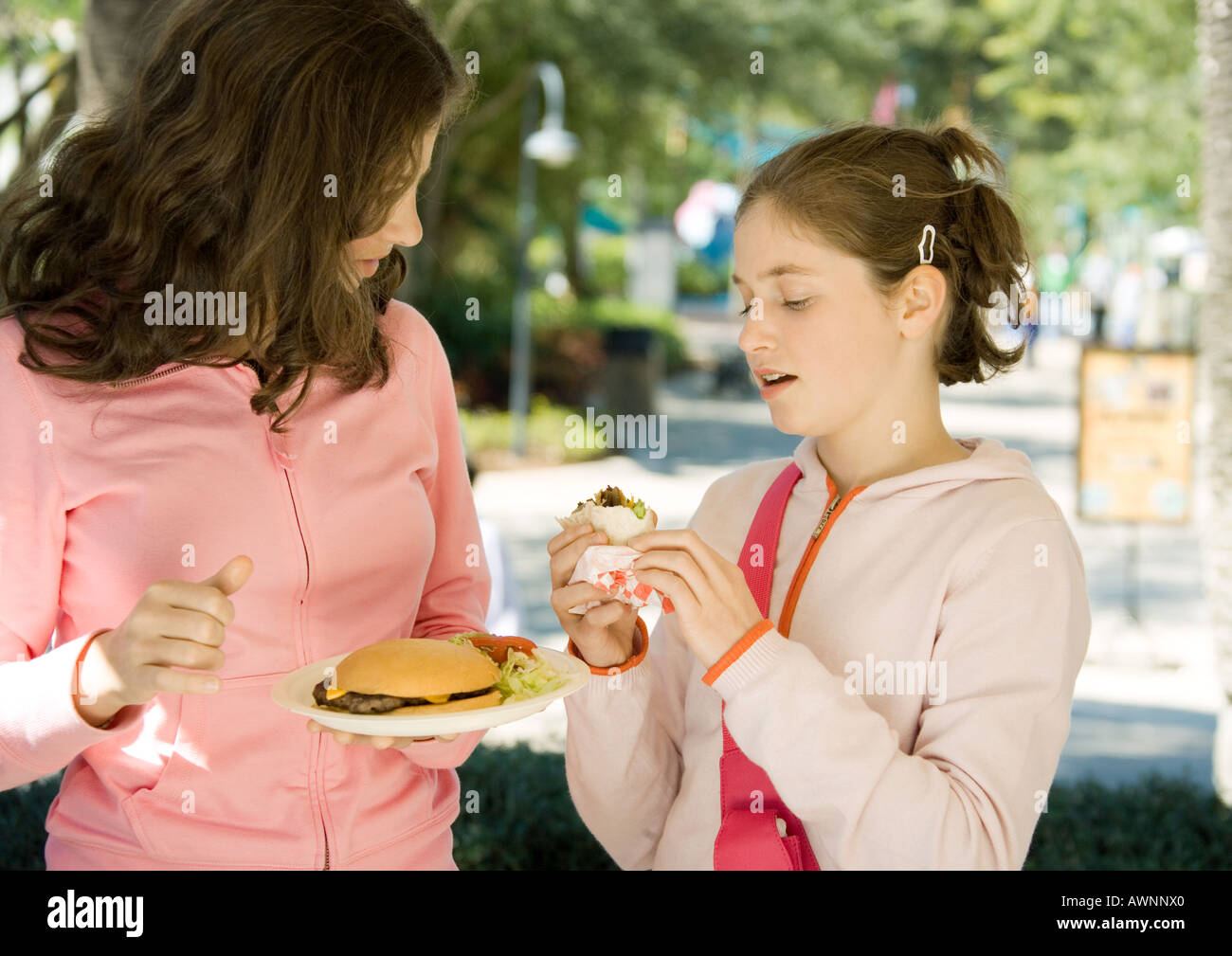 Two preteen girls eating junk food - Stock Image