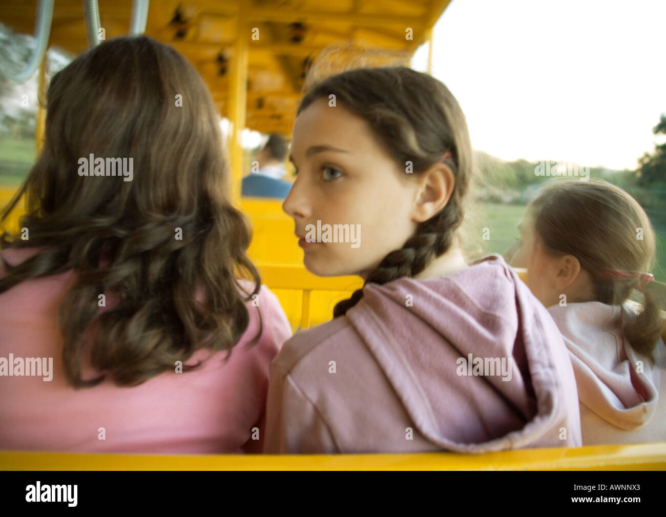 Preteen girls riding train in amusement park, rear view - Stock Image