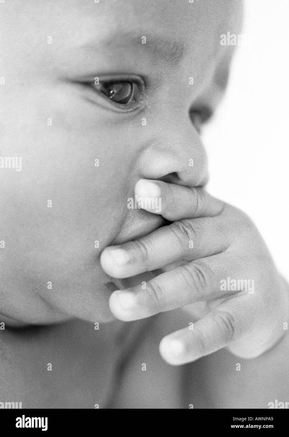 Baby with hand over mouth, close-up, b&w - Stock Image