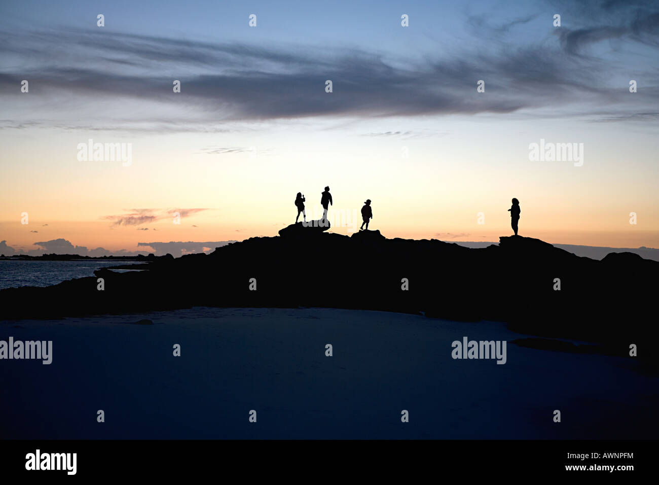 Silhouetted people on rocks - Stock Image