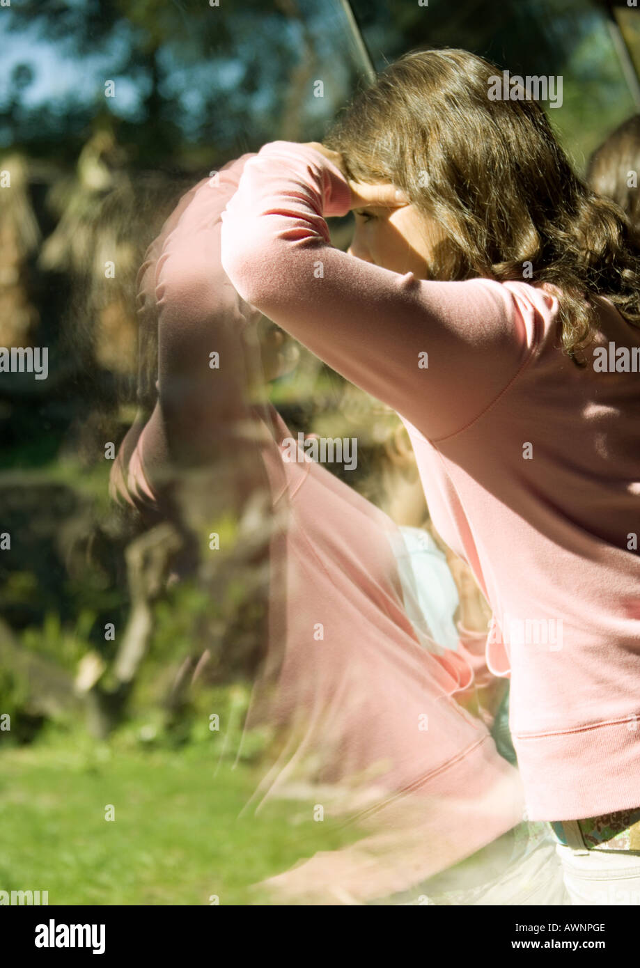 Girl looking through glass - Stock Image