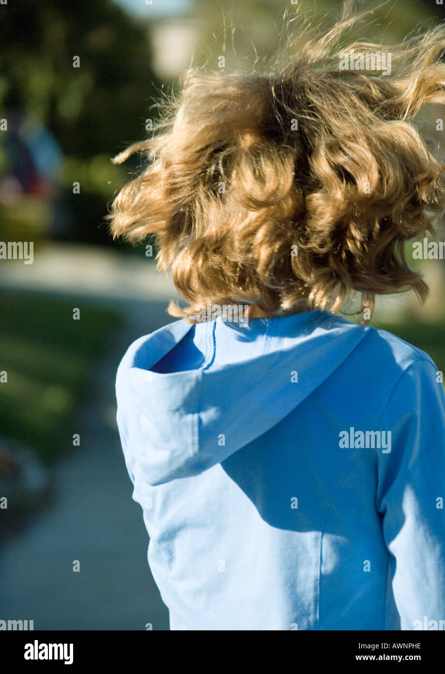 Girl with hair being tousled, rear view - Stock Image