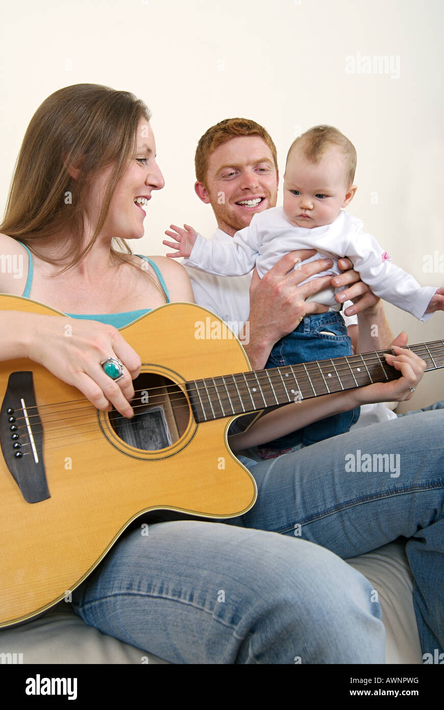 Mother playing guitar for her baby daughter - Stock Image
