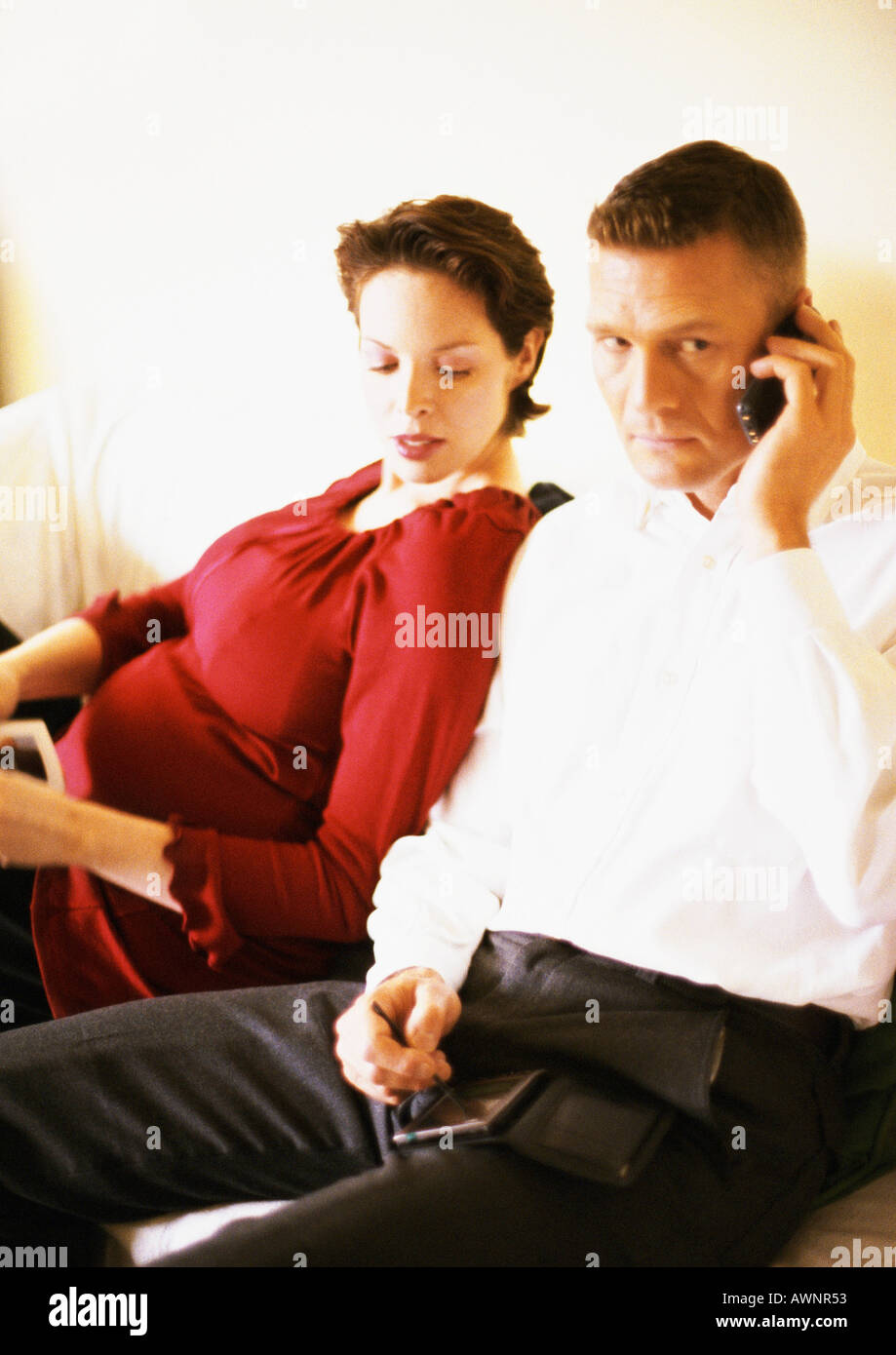 Pregnant woman sitting with man using cell phone - Stock Image
