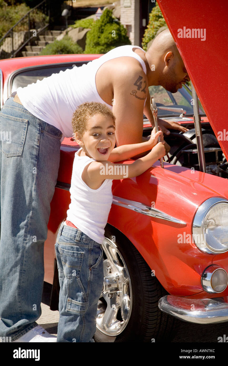 Young boy holding tools for his mechanic father - Stock Image