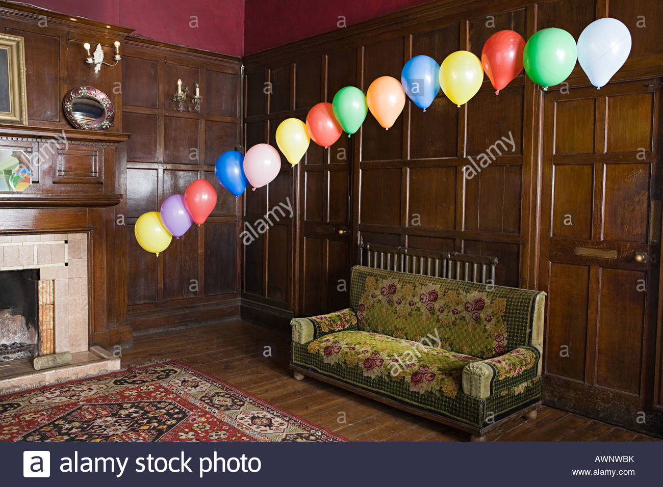Balloons floating in a lounge - Stock Image
