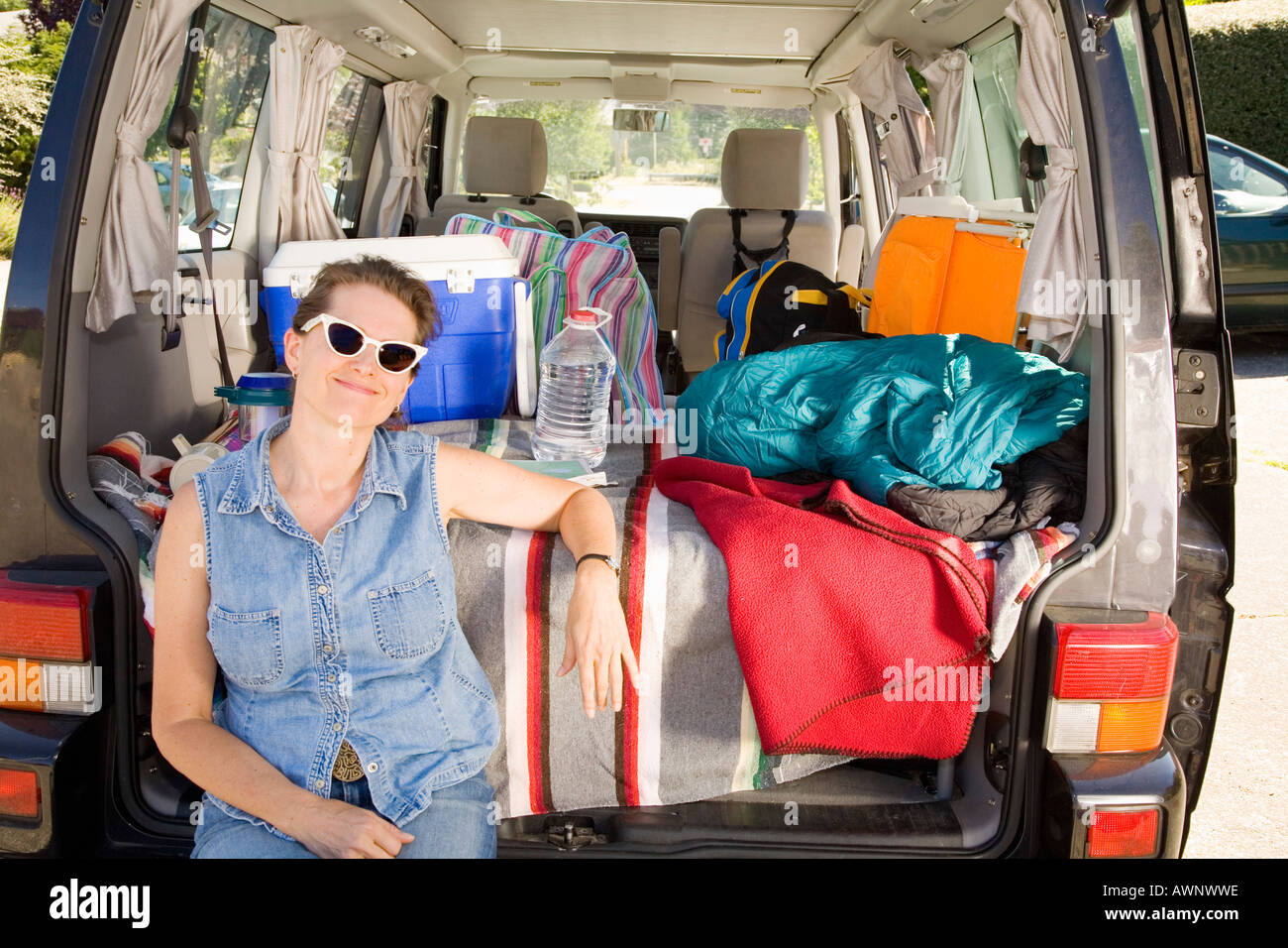 Woman sitting in trunk of car with camping gear Stock Photo