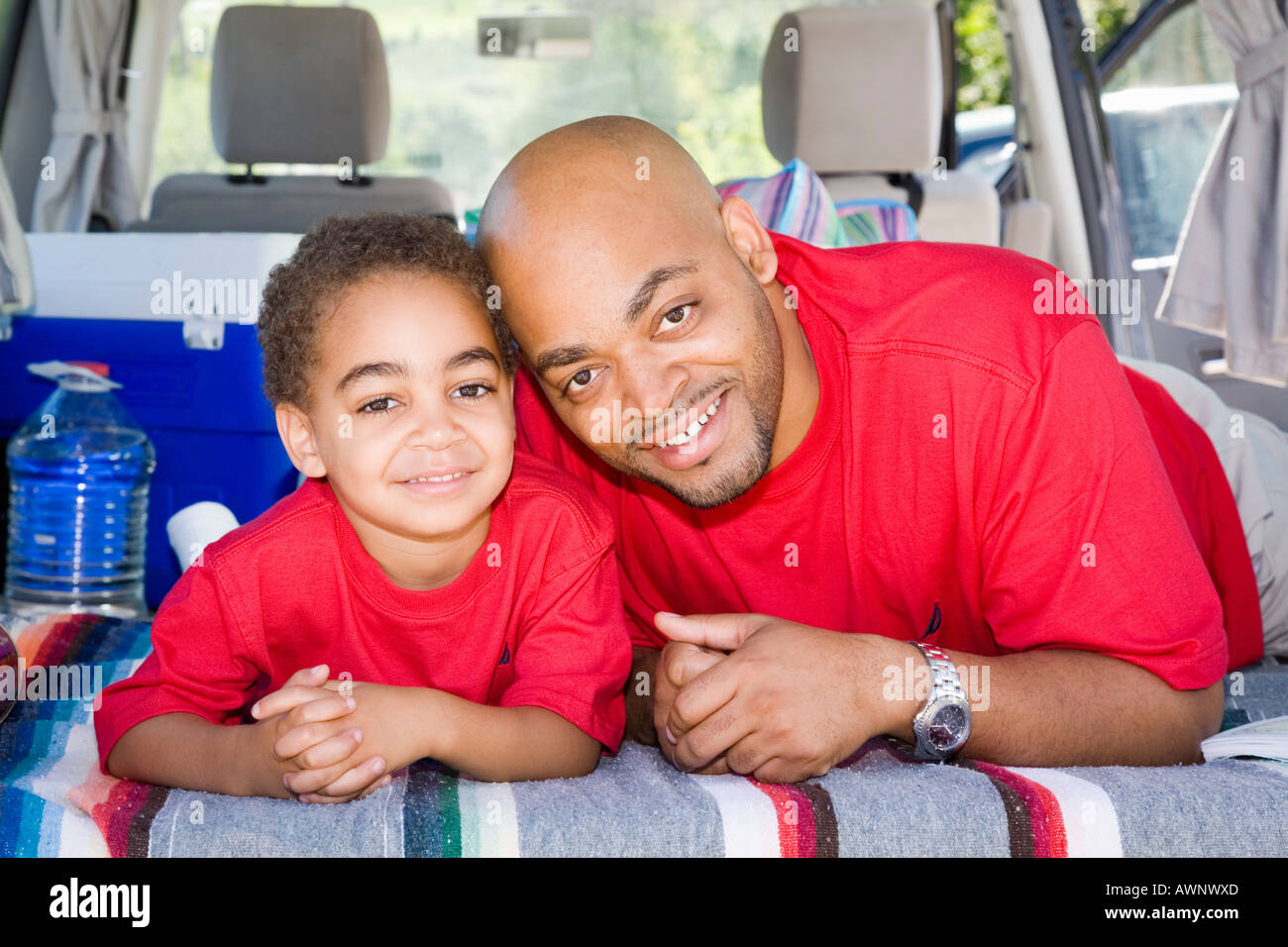 Father and son sitting in trunk of car with camping gear - Stock Image