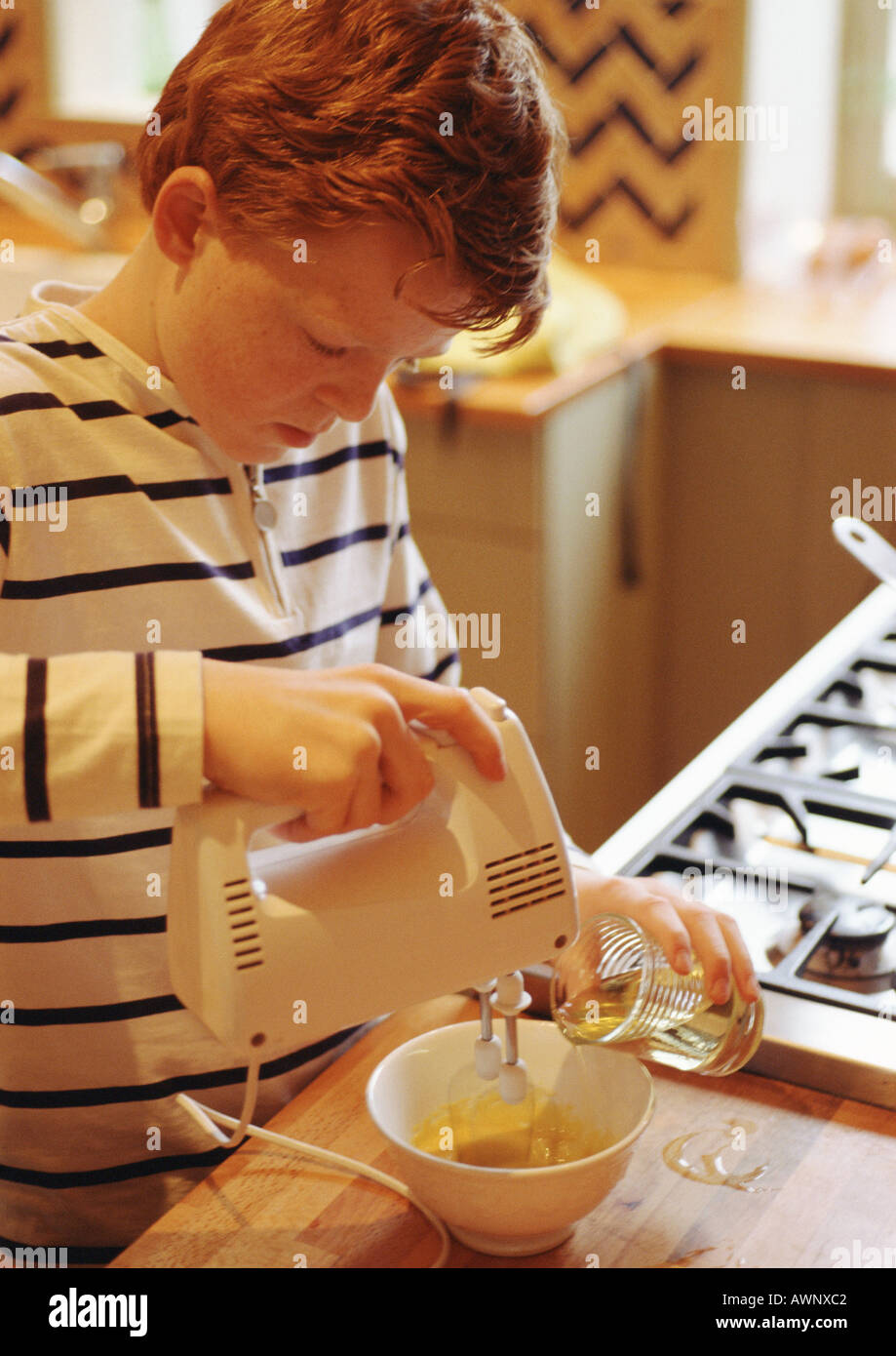 Child using electric mixer - Stock Image