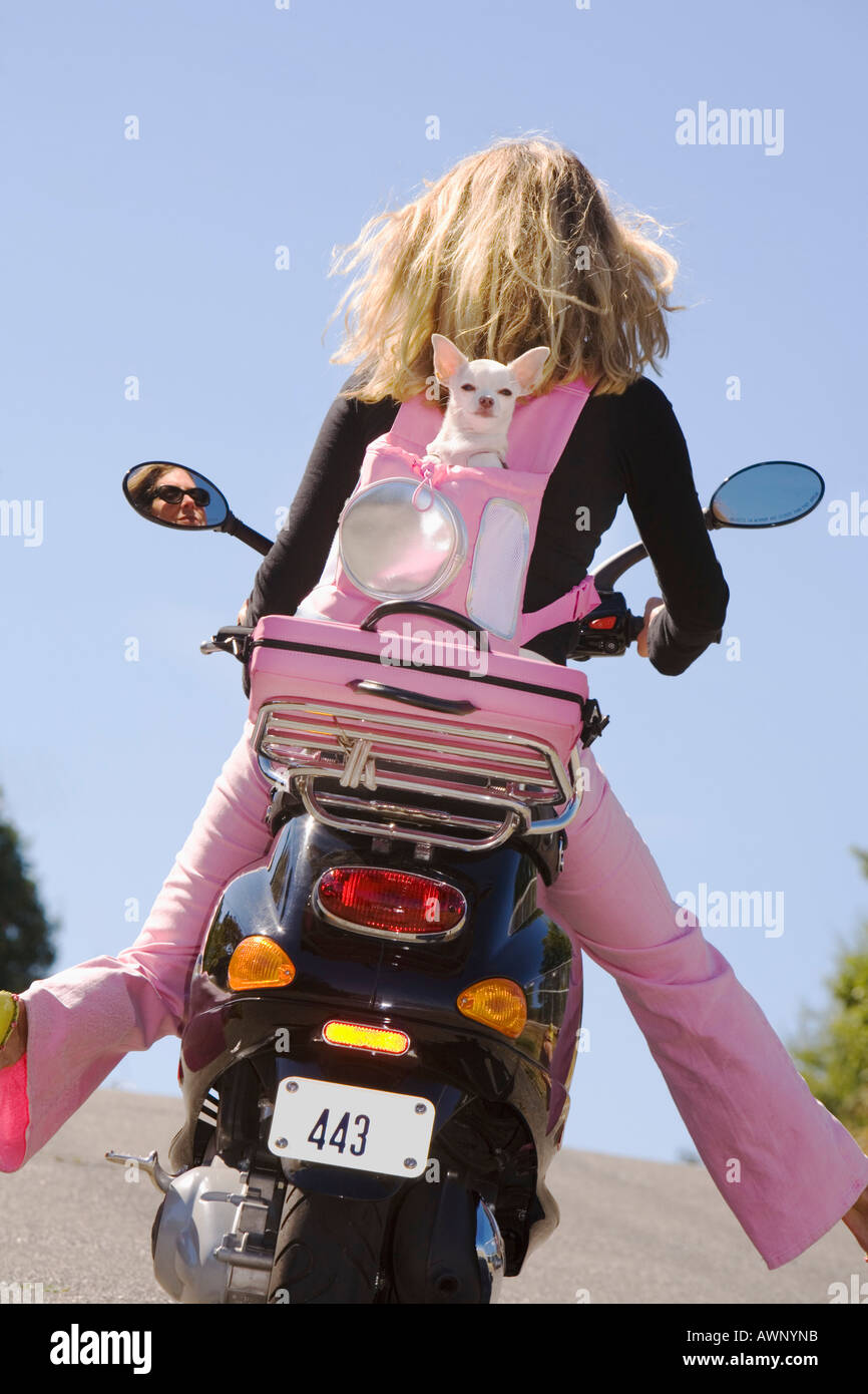 Woman riding a scooter with extended legs Stock Photo