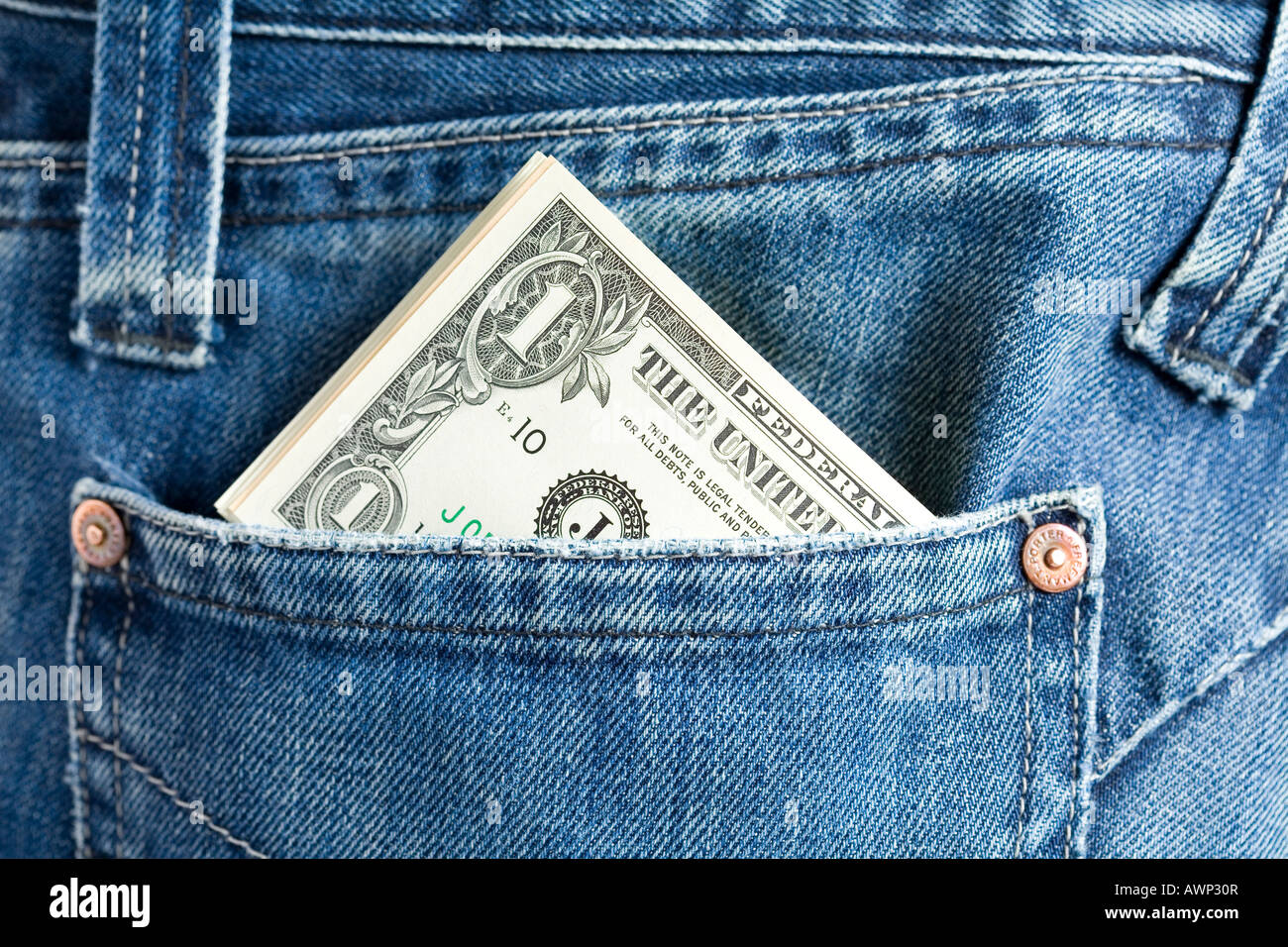 Cash (US dollars) sticking out of a jeans pocket - Stock Image