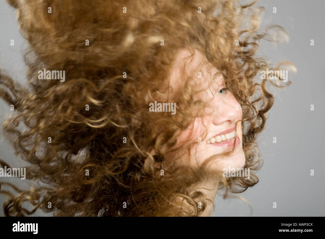Young woman, her long curly hair flying through the air - Stock Image