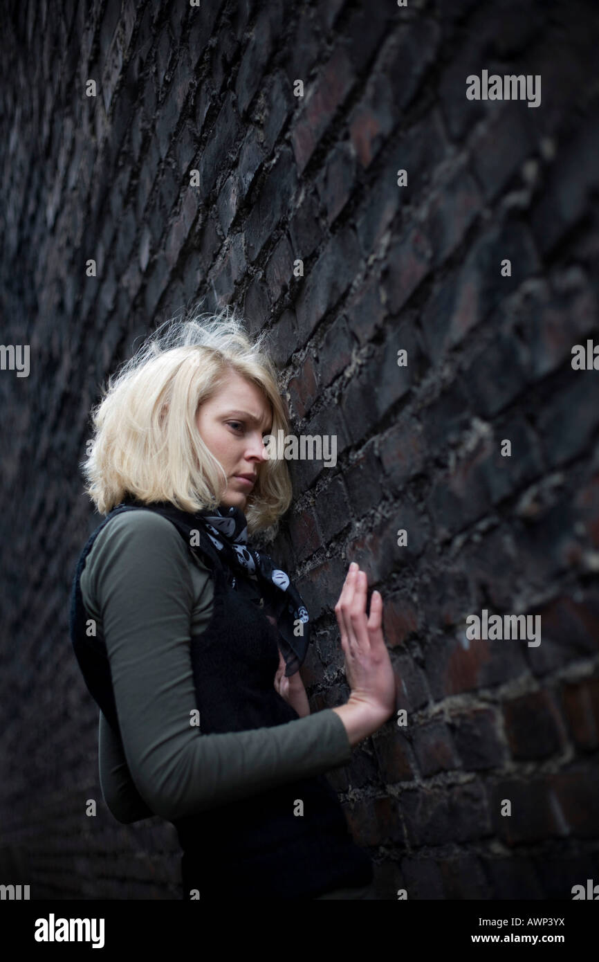 Blonde woman standing in front of a stone wall - Stock Image