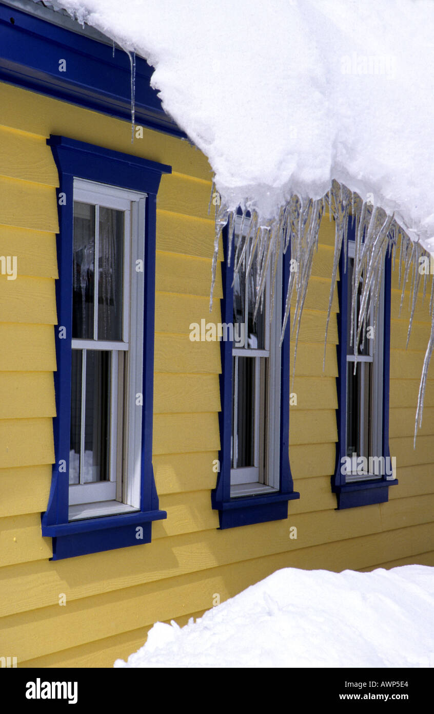 Icicles hanging from a snow laden roof overlooking a blue